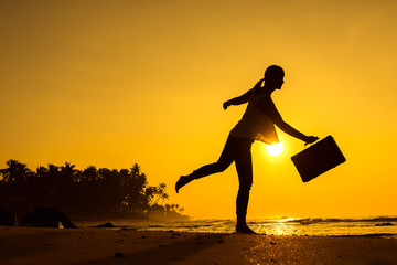 Female Silhouette staying along Ocean Coast with Luggage Bag enjoying scenic View Sea and Sunrise on background. Beach Holiday Concept.
