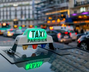 illuminated taxi Parsien sign over blurred Paris boulevard.