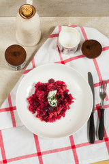 Risotto with beetroots, beets. Beige background, white plates.