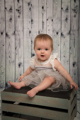 pretty baby in the studio on a wood background