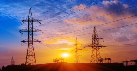 Silhouette of high voltage electrical pole. Sunset sky background.