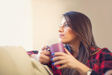 Attractive young woman drinking coffee at home looking to the window and daydreaming