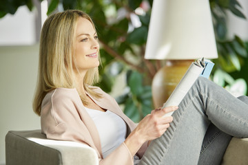 Enjoy relaxing at home. Shot of a beautiful middle aged woman reading magazine.