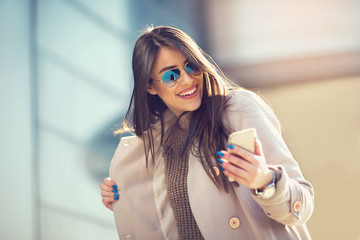 Beautiful brunette woman looking at mobile phone outdoor