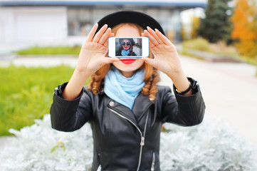 Fashion woman taking photo self portrait on smartphone in city closeup screen