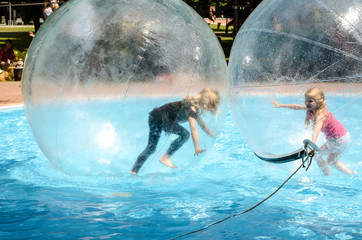 two children playing in super ball in swimming pool