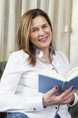 Charming mid age lady enjoying being at home and reading a book