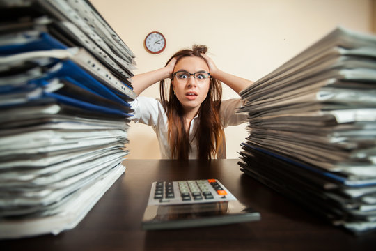 Doomed accountant against big stacks of documents