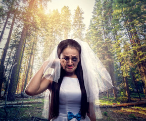 Bride with tearful face, pine forest on background