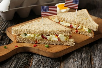Mayonnaise egg sandwich with American flag on top, selective focus