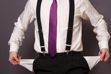Geschäftsmann mit Hosenträgern zeigt leere Hosentaschen