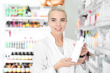Female shop assistant with bottle at work