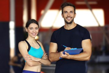 Woman with personal trainer preparing training plan in gym