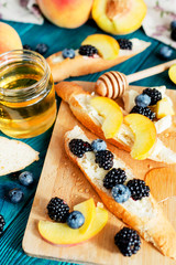 sweet snack , bruschetta with berries and fruits , blueberries , blackberries and peaches , with butter and honey on wooden background