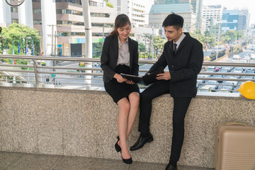 Two young business sitting looking file a report with in the city.