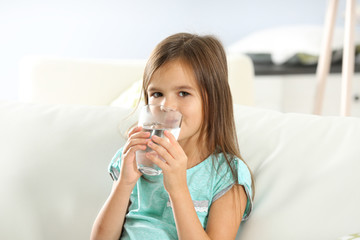 Cute little girl drinking water on sofa at home