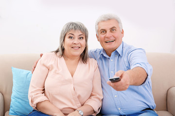 Middle aged couple watching TV at home