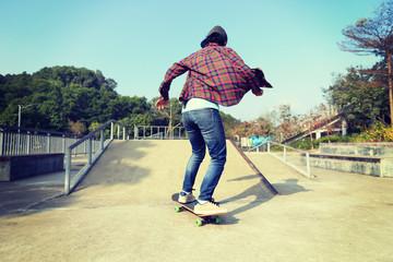 young skateboarder riding skateboard at skatepark