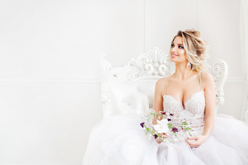 Young bride is sitting in white armchair