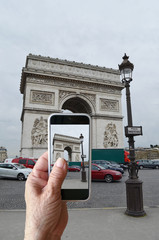 Seniors are shooting . old people taking pictures with his Smart Phone The Arc de Triomphe Place Charles de Gaulle in Paris, France . During a trip to through Europe.