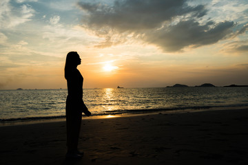 Silhouette women watching the sunset at the beach.
