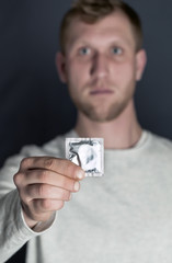 Hand of  young man holds packing of condoms. Blurred face