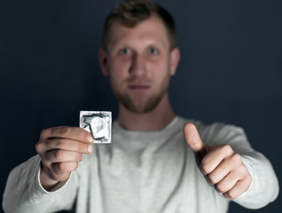 Hand of  young man holds packing of condoms and shows  finger up