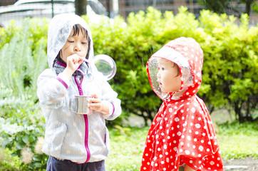 子供 雨の中でシャボン玉