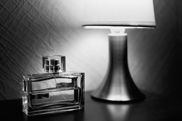 Table lamp with shade burlap burning on a wooden table and a bottle of men's fragrances. Black-and-white picture.
