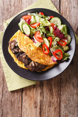 Austrian Imperial Steak with mushrooms, scrambled eggs and fresh salad closeup. vertical top view