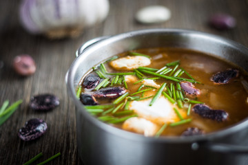 Bean Soup in Metal Pot with Raw Ingredients - Garlic and Chives on Wooden Background