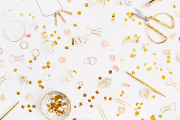 Beauty blog background. Gold style feminine accessories. Golden tinsel, scissors, pen, rings, necklace, bracelet on white background. Flat lay, top view.
