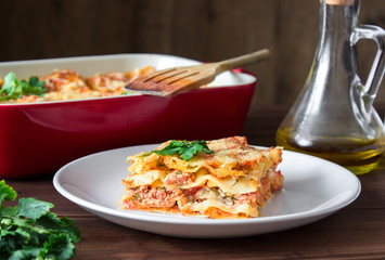 Close-up of a traditional lasagna topped with parskey leafs served on a white plate