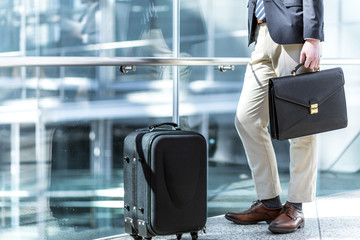 young man standing by handrail with suit case