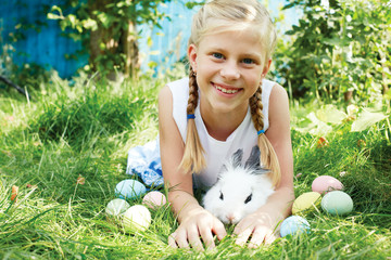 Child hunted on Easter egg  in blooming spring garden. Child with white bunny  searching for colorful eggs on meadow.