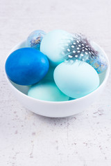 Plate with painted blue eggs on wooden table desktop