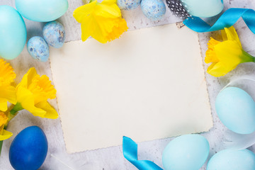Easter frame with painted eggs and yellow daffodil flowers