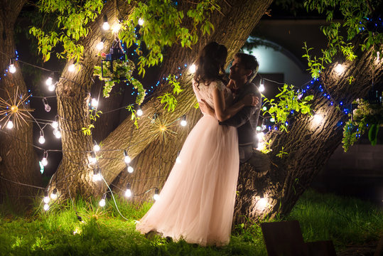 wedding couple in magical night forest decorated light garlands