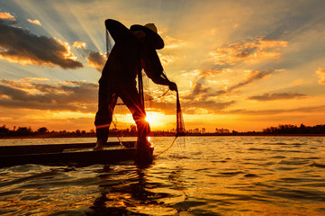 Silluate fisherman and boat in river on during sunrset,Thailand