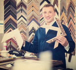 professional man seller in picture framing studio with wooden details