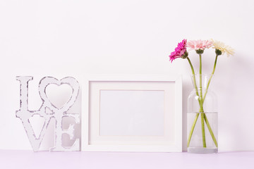 Blank frame and bouquet of flowers on the table, mock up
