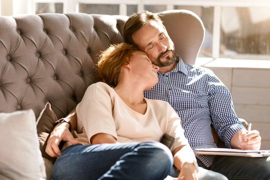 Relaxed peaceful middle aged couple resting at home