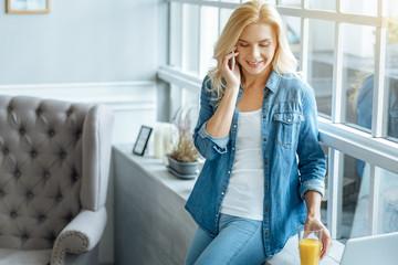 Joyful woman talking on a cellphone