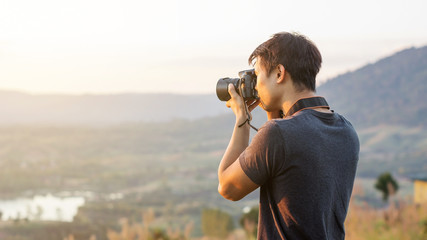 Men travel and take a photo of the sunset at the mountain.