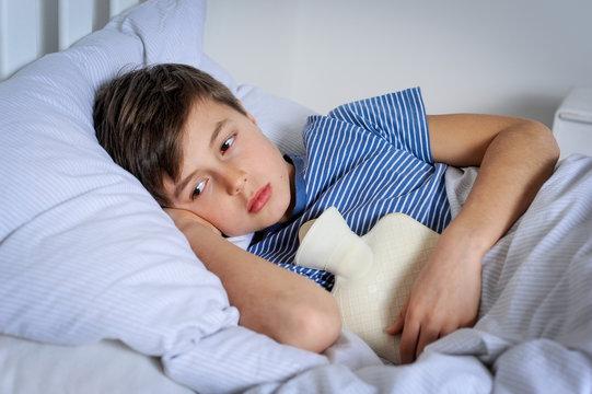 Kind mit Wärmflasche und Bauchschmerzen im Bett liegend