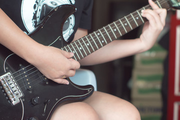 Playing electric guitar black by women hand