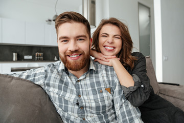 Young funny loving couple sitting on sofa indoors