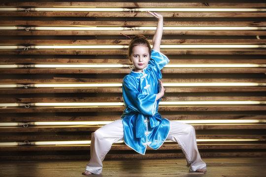 Pretty little girl in the room in sportswear for martial arts is Wushu