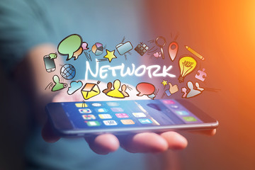 Concept of man holding smartphone with network title and multimedia icons flying around