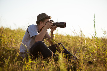 Young male photographer in hat taking picture, sitting in field.